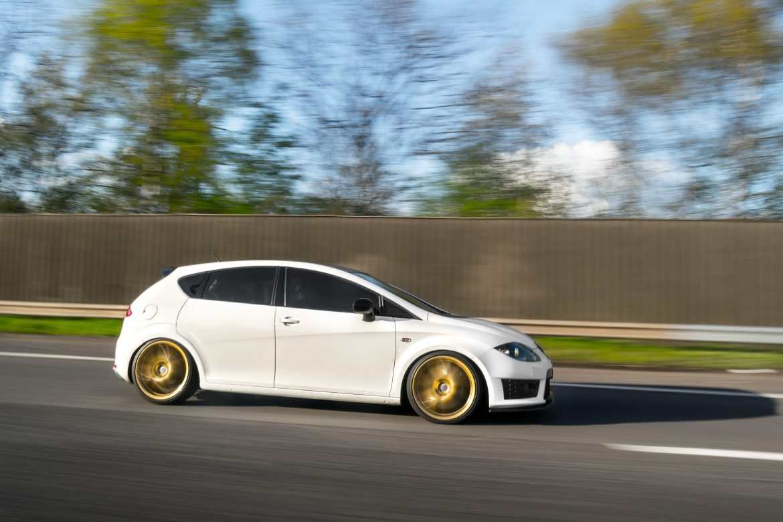 Rolling shot of Seat Leon Cupra R on gold wheels